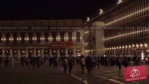Купить «Piazza San Marco with lots of people walking there at night. Venice, Italy», видеоролик № 29082673, снято 23 апреля 2018 г. (c) Данил Руденко / Фотобанк Лори
