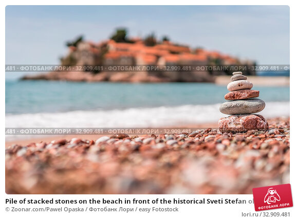 Pile of stacked stones on the beach in front of the historical Sveti Stefan old town, coast of Montenegro. Стоковое фото, фотограф Zoonar.com/Pawel Opaska / easy Fotostock / Фотобанк Лори
