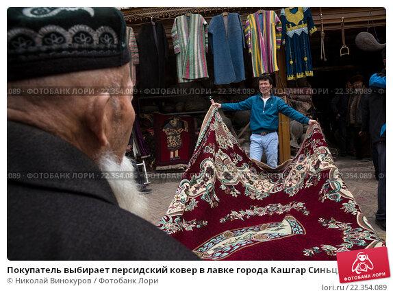 Купить «Покупатель выбирает персидский ковер в лавке города Кашгар Синьцзян-Уйгурского автономного района Китая», фото № 22354089, снято 18 марта 2016 г. (c) Николай Винокуров / Фотобанк Лори