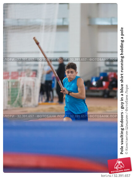 Купить «Pole vaulting indoors - guy in a blue shirt running holding a pole», фото № 32391657, снято 1 ноября 2019 г. (c) Константин Шишкин / Фотобанк Лори