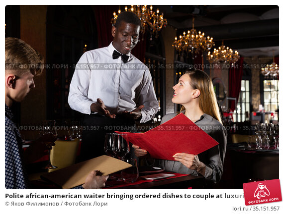 Polite african-american waiter bringing ordered dishes to couple at luxurious restaurant. Стоковое фото, фотограф Яков Филимонов / Фотобанк Лори