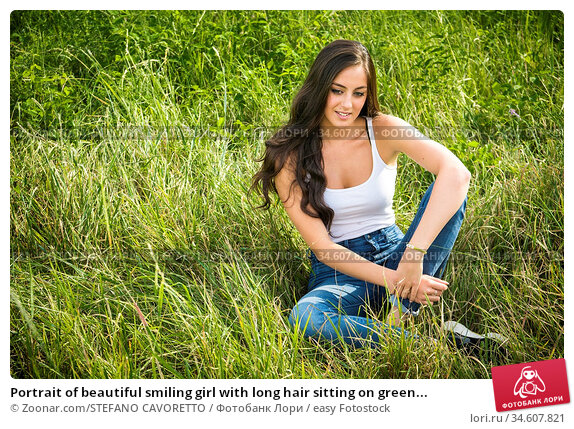 Portrait of beautiful smiling girl with long hair sitting on green... Стоковое фото, фотограф Zoonar.com/STEFANO CAVORETTO / easy Fotostock / Фотобанк Лори