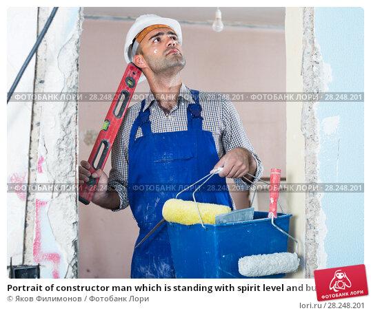 Купить «Portrait of constructor man which is standing with spirit level and bucket», фото № 28248201, снято 18 мая 2017 г. (c) Яков Филимонов / Фотобанк Лори