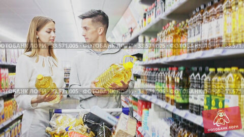 Portrait of friendly man and woman with shopping cart choosing olive oil in supermarket. Стоковое видео, видеограф Яков Филимонов / Фотобанк Лори