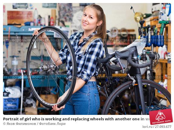 Купить «Portrait of girl who is working and replacing wheels with another one in workshop.», фото № 27093677, снято 13 сентября 2017 г. (c) Яков Филимонов / Фотобанк Лори