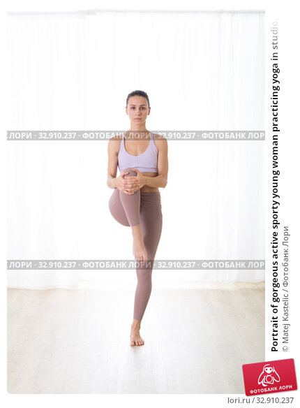 Portrait of gorgeous active sporty young woman practicing yoga in studio. Beautiful girl practice Tadasana, tree yoga pose. Healthy active lifestyle, working out indoors in gym. Стоковое фото, фотограф Matej Kastelic / Фотобанк Лори