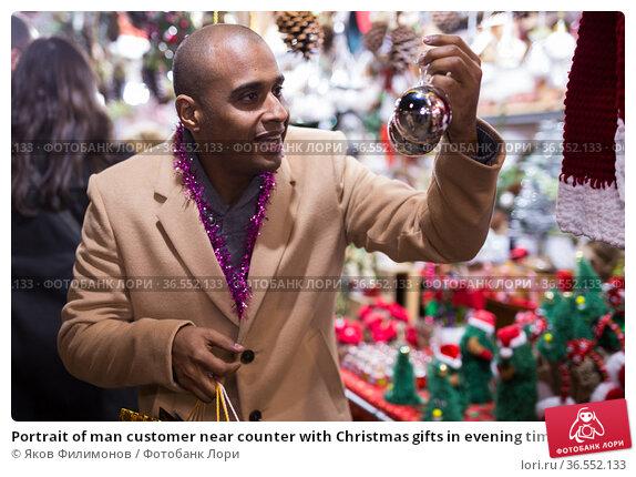 Portrait of man customer near counter with Christmas gifts in evening time. Стоковое фото, фотограф Яков Филимонов / Фотобанк Лори