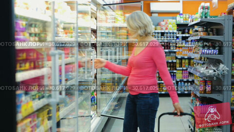 Купить «Portrait of mature woman choosing fresh dairy products on shelves in grocery shop», видеоролик № 30617029, снято 27 февраля 2019 г. (c) Яков Филимонов / Фотобанк Лори