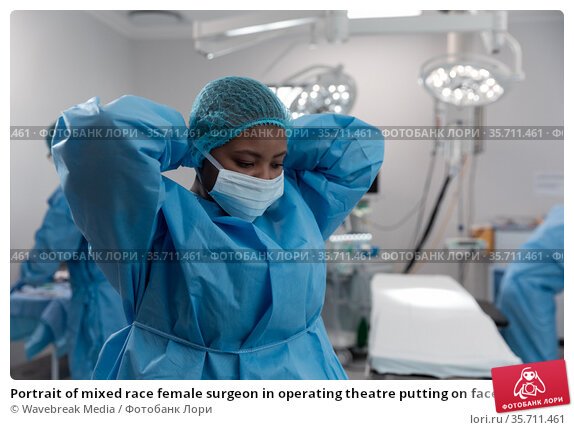 Portrait of mixed race female surgeon in operating theatre putting on face mask. Стоковое фото, агентство Wavebreak Media / Фотобанк Лори