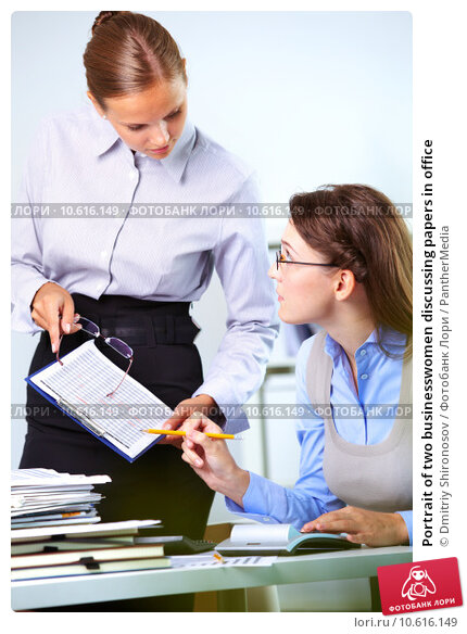 Portrait of two businesswomen discussing papers in office. Стоковое фото, фотограф Dmitriy Shironosov / PantherMedia / Фотобанк Лори