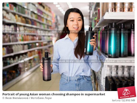 Portrait of young Asian woman choosing shampoo in supermarket. Стоковое фото, фотограф Яков Филимонов / Фотобанк Лори