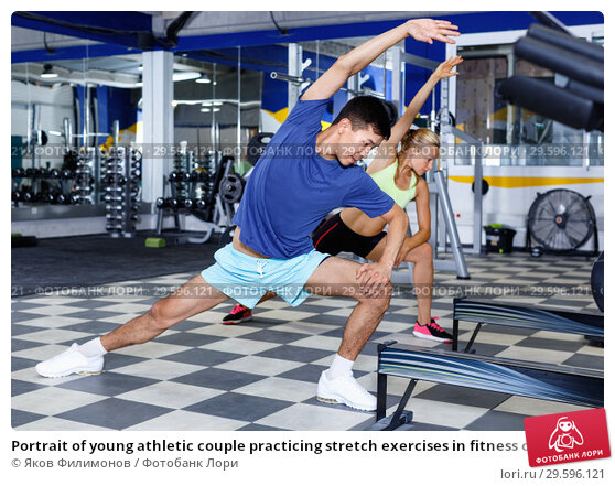 Купить «Portrait of young athletic couple practicing stretch exercises in fitness center», фото № 29596121, снято 16 июля 2018 г. (c) Яков Филимонов / Фотобанк Лори