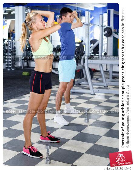 Portrait of young athletic couple practicing stretch exercises in fitness center. Стоковое фото, фотограф Яков Филимонов / Фотобанк Лори