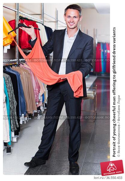 Portrait of young cheerful man offering to girlfriend dress variants. Стоковое фото, фотограф Яков Филимонов / Фотобанк Лори