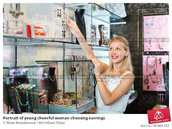 Купить «Portrait of young cheerful woman choosing earrings», фото № 30803321, снято 26 июня 2019 г. (c) Яков Филимонов / Фотобанк Лори