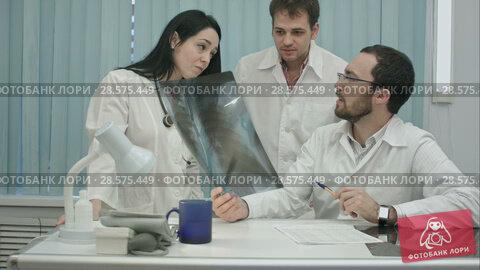 Купить «Portrait of young group of doctors looking at x-ray», видеоролик № 28575449, снято 24 ноября 2015 г. (c) Vasily Alexandrovich Gronskiy / Фотобанк Лори