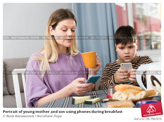 Portrait of young mother and son using phones during breakfast. Стоковое фото, фотограф Яков Филимонов / Фотобанк Лори