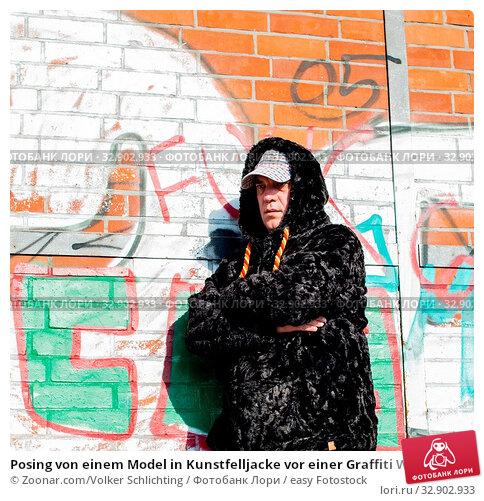 Posing von einem Model in Kunstfelljacke vor einer Graffiti Wand Posing of a Man model in Faux fur jacket in front of a graffiti wall. Стоковое фото, фотограф Zoonar.com/Volker Schlichting / easy Fotostock / Фотобанк Лори