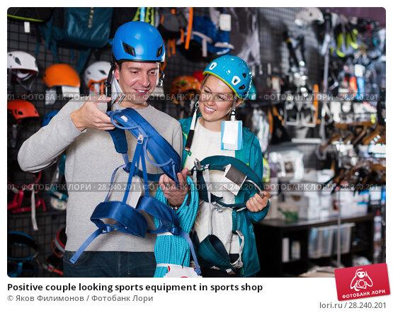 Купить «Positive couple looking sports equipment in sports shop», фото № 28240201, снято 25 октября 2017 г. (c) Яков Филимонов / Фотобанк Лори