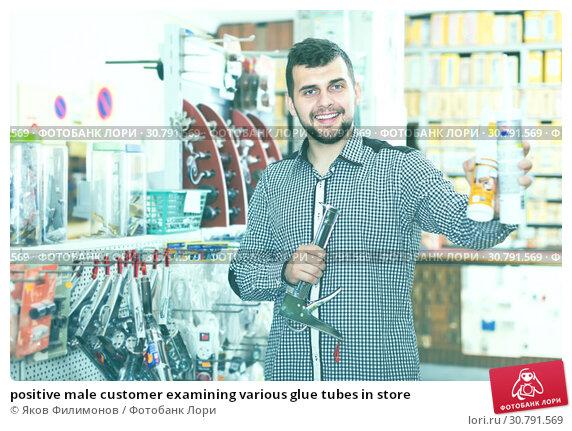 Купить «positive male customer examining various glue tubes in store», фото № 30791569, снято 5 апреля 2017 г. (c) Яков Филимонов / Фотобанк Лори