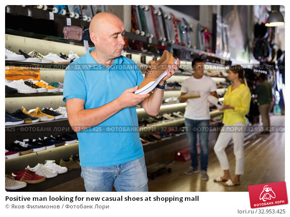 Positive man looking for new casual shoes at shopping mall. Стоковое фото, фотограф Яков Филимонов / Фотобанк Лори