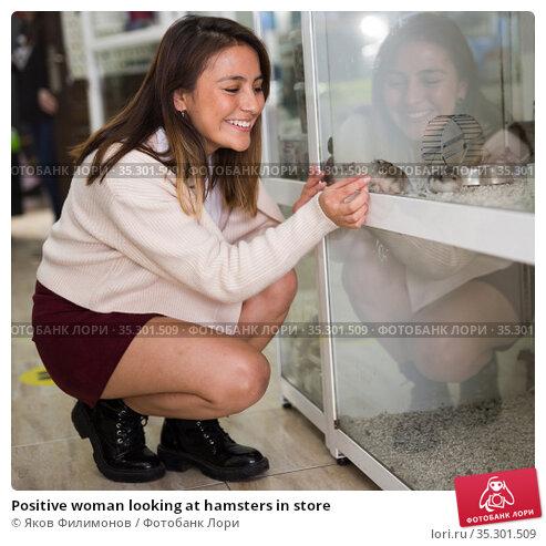 Positive woman looking at hamsters in store. Стоковое фото, фотограф Яков Филимонов / Фотобанк Лори