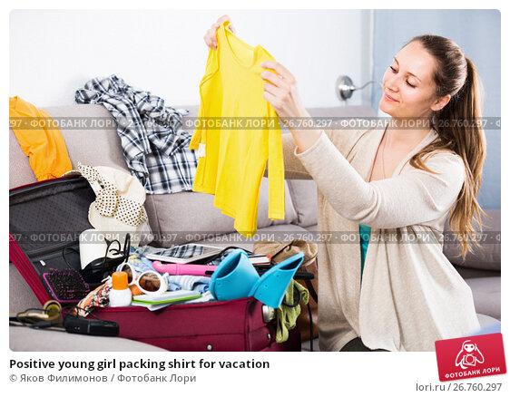 Купить «Positive young girl packing shirt for vacation», фото № 26760297, снято 21 марта 2017 г. (c) Яков Филимонов / Фотобанк Лори