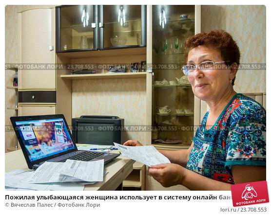 Пожилая улыбающаяся женщина использует в систему онлайн банка для оплаты счетов, эксклюзивное фото № 23708553, снято 19 июня 2016 г. (c) Вячеслав Палес / Фотобанк Лори