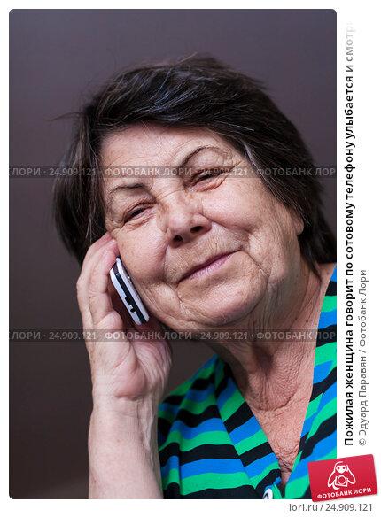 Купить «Пожилая женщина говорит по сотовому телефону улыбается и смотрит в кадр», фото № 24909121, снято 6 января 2017 г. (c) Эдуард Паравян / Фотобанк Лори