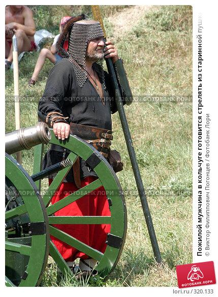 Пожилой мужчина в кольчуге готовится стрелять из старинной пушки, фото № 320133, снято 7 августа 2005 г. (c) Виктор Филиппович Погонцев / Фотобанк Лори