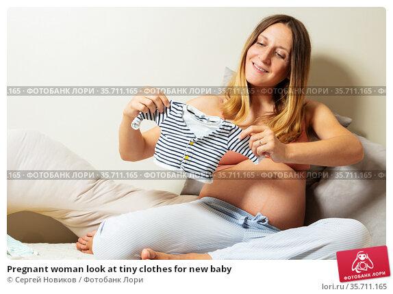 Pregnant woman look at tiny clothes for new baby. Стоковое фото, фотограф Сергей Новиков / Фотобанк Лори
