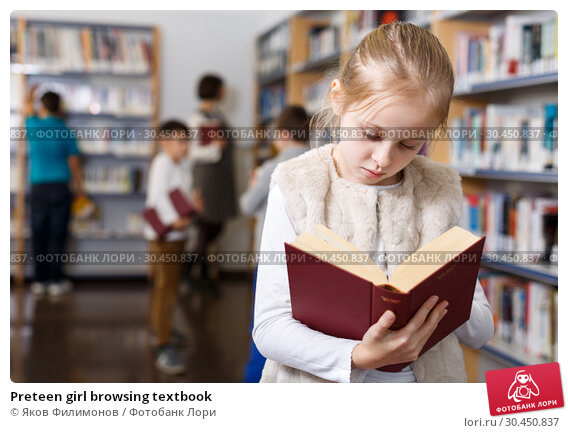 Preteen girl browsing textbook. Стоковое фото, фотограф Яков Филимонов / Фотобанк Лори