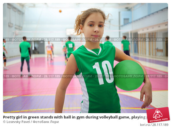 Купить «Pretty girl in green stands with ball in gym during volleyball game, playing people out of focus», фото № 28117189, снято 23 октября 2016 г. (c) Losevsky Pavel / Фотобанк Лори