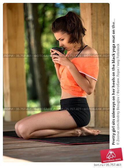 Pretty girl sits sideways on her heels on the black yoga mat on the... Стоковое фото, фотограф Zoonar.com/Andrey Bezuglov / easy Fotostock / Фотобанк Лори