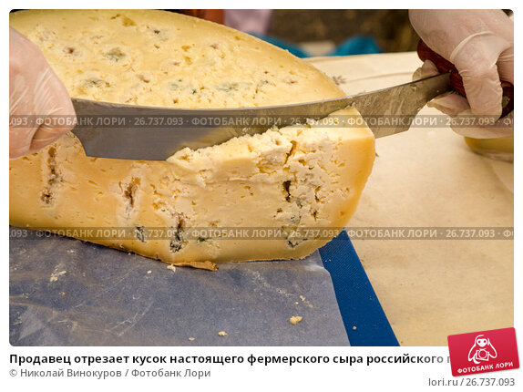 Продавец отрезает кусок настоящего фермерского сыра российского производства в магазине, фото № 26737093, снято 6 августа 2017 г. (c) Николай Винокуров / Фотобанк Лори