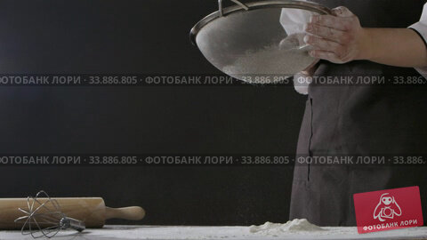 Купить «Professional chief sieves flour with sifter on a dark wooden table on a black background. Slow motion, Full HD video, 240fps, 1080p. Process preparing of homemade pastry.», видеоролик № 33886805, снято 2 июля 2020 г. (c) Ярослав Данильченко / Фотобанк Лори
