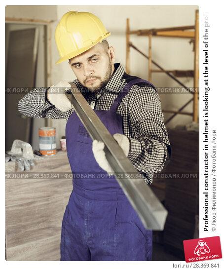 Купить «Professional constructor in helmet is looking at the level of the profile», фото № 28369841, снято 3 июня 2017 г. (c) Яков Филимонов / Фотобанк Лори