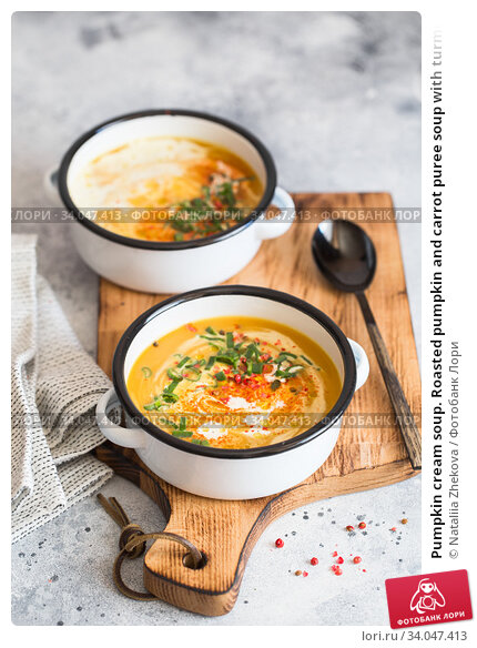 Pumpkin cream soup. Roasted pumpkin and carrot puree soup with turmeric, cream, paprica, chives and pumpkin seeds on grey background. Vegetarian and Vegan recipe. Green living. Organic food. Стоковое фото, фотограф Nataliia Zhekova / Фотобанк Лори