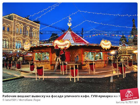 Купить «Рабочие вешают вывеску на фасаде уличного кафе. ГУМ-ярмарка на Красной площади в Москве вечером», эксклюзивное фото № 6757181, снято 3 декабря 2014 г. (c) lana1501 / Фотобанк Лори
