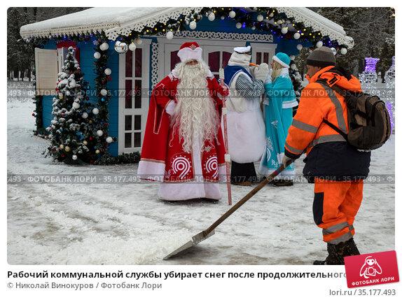 Рабочий коммунальной службы убирает снег после продолжительного снегапада во время новогодних праздников на фоне резиденции Деда Мороза в парке на Речном вокзале в городе Москве, Россия. Редакционное фото, фотограф Николай Винокуров / Фотобанк Лори