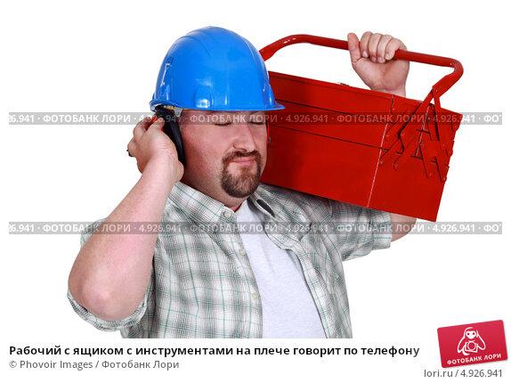 Рабочий с ящиком с инструментами на плече говорит по телефону. Стоковое фото, фотограф Phovoir Images / Фотобанк Лори