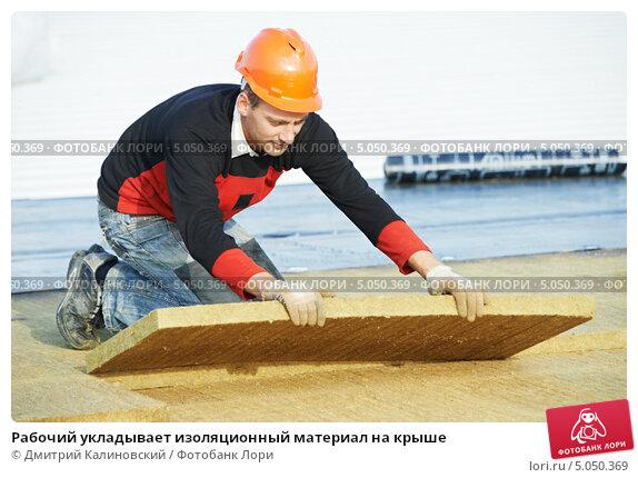 Купить «Рабочий укладывает изоляционный материал на крыше», фото № 5050369, снято 18 октября 2012 г. (c) Дмитрий Калиновский / Фотобанк Лори