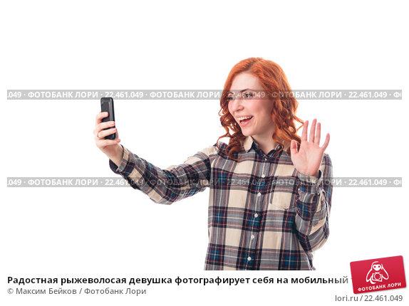 Купить «Радостная рыжеволосая девушка фотографирует себя на мобильный телефон», фото № 22461049, снято 5 июля 2020 г. (c) Максим Бейков / Фотобанк Лори