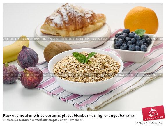 Raw oatmeal in white ceramic plate, blueberries, fig, orange, banana... Стоковое фото, фотограф Natalya Danko / easy Fotostock / Фотобанк Лори