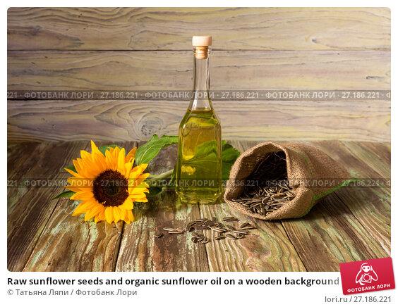 Купить «Raw sunflower seeds and organic sunflower oil on a wooden background close-up», фото № 27186221, снято 7 ноября 2017 г. (c) Татьяна Ляпи / Фотобанк Лори