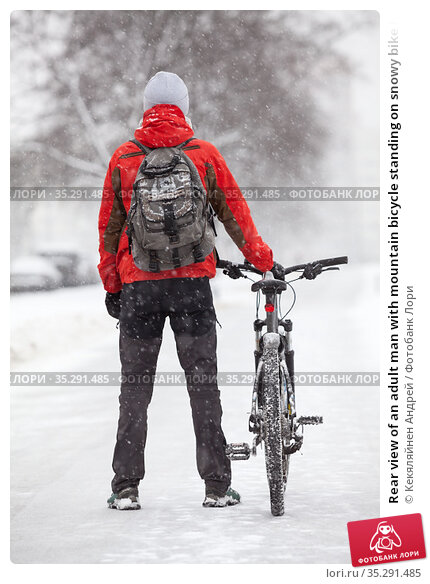 Rear view of an adult man with mountain bicycle standing on snowy bike lane on an urban streets, winter season with snowfall. Стоковое фото, фотограф Кекяляйнен Андрей / Фотобанк Лори