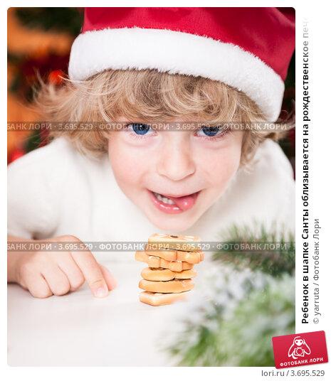 Купить «Ребенок в шапке Санты облизывается на рождественское печенье», фото № 3695529, снято 27 апреля 2012 г. (c) yarruta / Фотобанк Лори