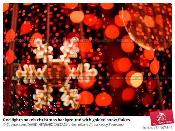 Red lights bokeh christmas background with golden snow flakes. Стоковое фото, фотограф Zoonar.com/DAVID HERRAEZ CALZADA / easy Fotostock / Фотобанк Лори