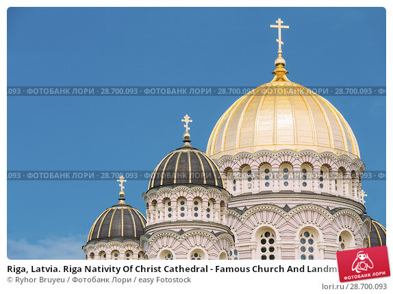 Купить «Riga, Latvia. Riga Nativity Of Christ Cathedral - Famous Church And Landmark. Close Up Of Golden Yellow Domes On Blue Sunny Sky Background At Summer Season.», фото № 28700093, снято 1 июля 2016 г. (c) easy Fotostock / Фотобанк Лори