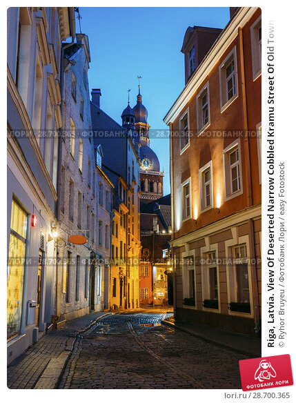 Купить «Riga, Latvia. View Of Deserted Narrow Cobbled Kramu Street Of Old Town In Bright Evening Illumination With Ancient Architecture Leading To Dome Cathedral Under Summer Blue Sky.», фото № 28700365, снято 1 июля 2016 г. (c) easy Fotostock / Фотобанк Лори